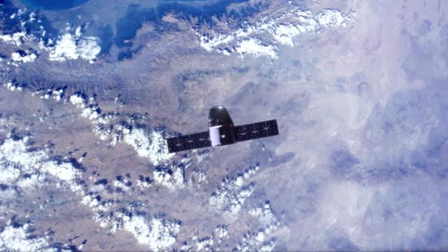 satellite with solar panels moving over earth - вид со спутника стоковые видео и кадры b-roll