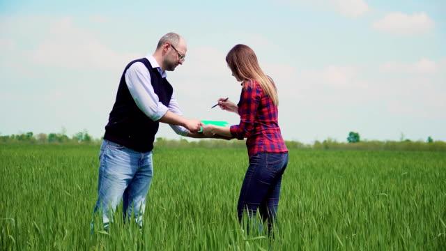 Nöjd kund är bonde kvinna köper fält med grödor och underteckna hyres avtal och hand skakning med man kontor mäklaren video