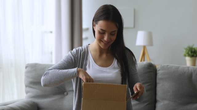 Satisfied female customer open parcel box sit on sofa
