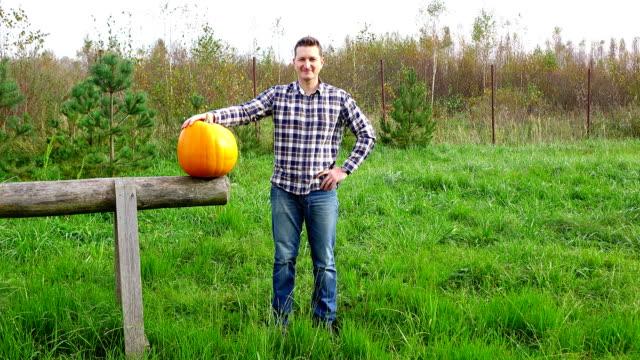 vidéos et rushes de stand jeune agriculteur satisfait des bonnes récoltes sur terrain avec grosse citrouille - enseignant(e)