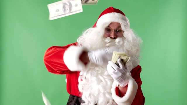vídeos de stock e filmes b-roll de satisfied santa claus throwing bills out of a bundle money in camera, money concept, green chromakey in the background - pai natal
