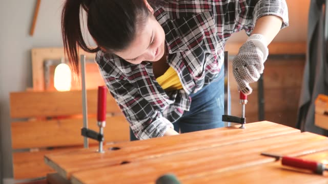 satisfied smiling young professional female carpentry worker with steel vise on the table in the workshop