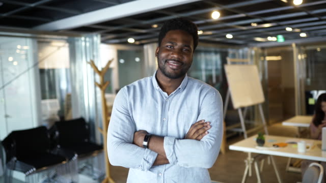 Satisfied With His Career Young African entrepreneur standing at the office of a multi-ethnic corporation. image stock videos & royalty-free footage