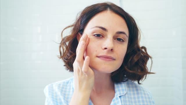 satisfied with my facial skin treatment results. - trattamento per la pelle video stock e b–roll