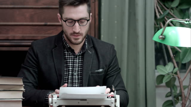 Satisfied writer finished typing his book and taking his glasses off video