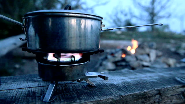 Saucepan is heated on the gas burner at the campsite video