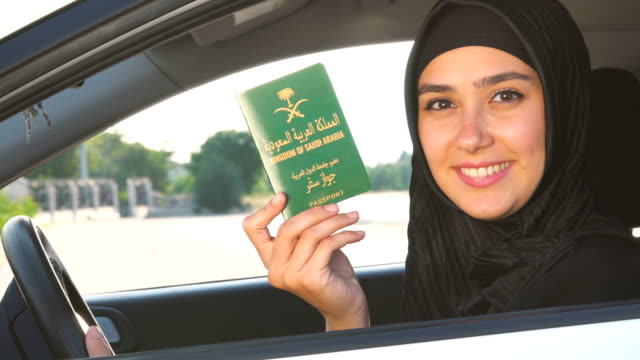 Saudi Arabian woman is holding her passport in the car Saudi Arabian woman finally is being allowed to travel independently and she is holding hers passport at the car // 4K 3840x2160 / 29.97p / Photo-JPEG / Real Time passport stock videos & royalty-free footage