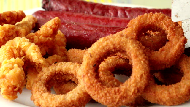 Sausage chicken and onion rings on a plate Delicious fried fast food plate with sausage,crispy chicken wings and onion ring onion ring stock videos & royalty-free footage