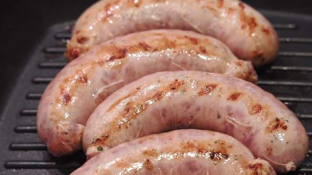 sausage on the grill pan,cooking in macro view, barbecue and Germany breakfast cooking homemade sausages on a grill pan. pork sausages are simmering on the barbecue grill, metal griddle. roast dinner stock videos & royalty-free footage