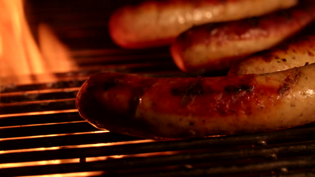 Sausages being grilled on a firey barbecue video