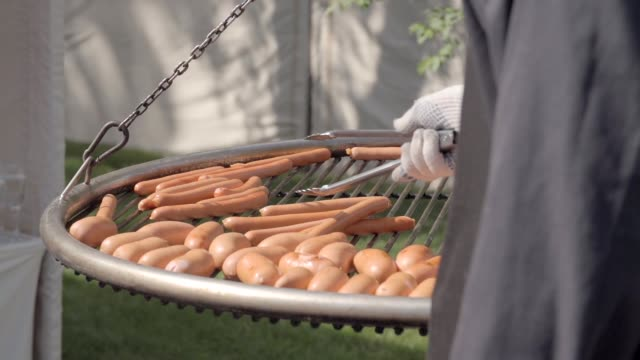 sausages grilled on a bbq - abbrustolito video stock e b–roll