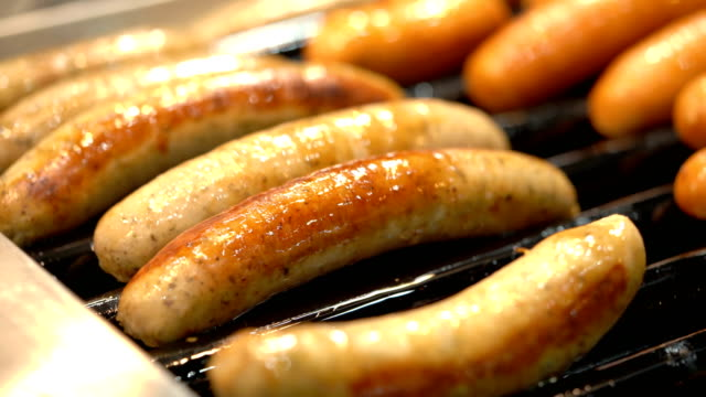 4K CU sausages on rolling grill Two close up shots of sausages cooked on rolling grill hot dog stock videos & royalty-free footage