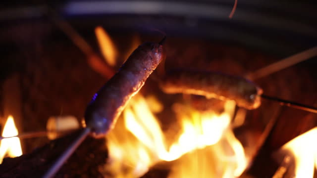 Sausages over campfire (extreme close-up) video