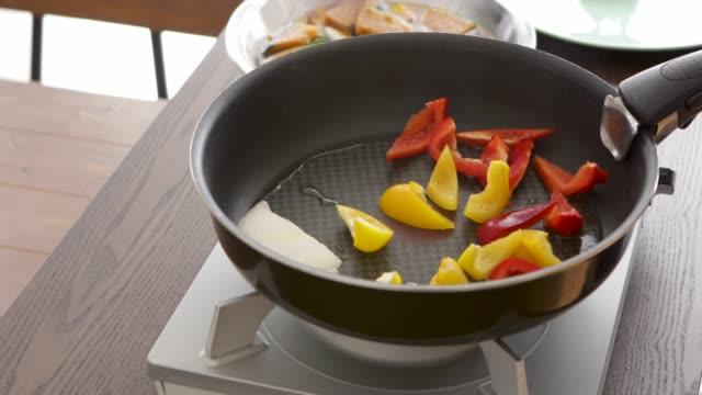 ソテー パプリカとフライパンで玉ねぎをパンします。 - 田舎のライフスタイル点の映像素材/bロール