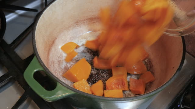 sautéing butternut squash cubes in a dutch oven in 4k - zucchini video stock e b–roll