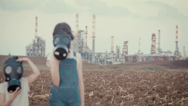 save the plant. kids wearing gas masks near an oil refinery - climate change video stock e b–roll