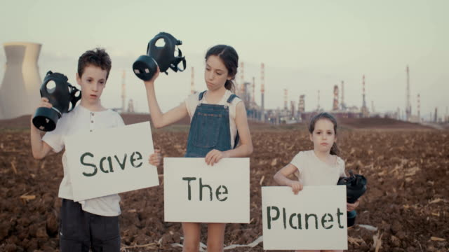 Save the plant. Young kids holding signs standing near a refinery with gas masks Save the planet. young kids holding signs standing with gas masks ecosystem stock videos & royalty-free footage