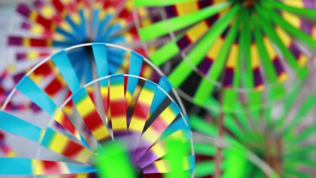 Save to Board Close-up Shot of Rotating Colorful Windmill Toy in Row