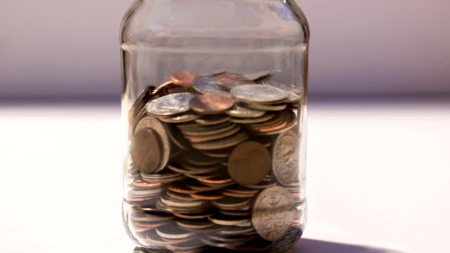 saving jar of money filling up with coins - risparmi video stock e b–roll