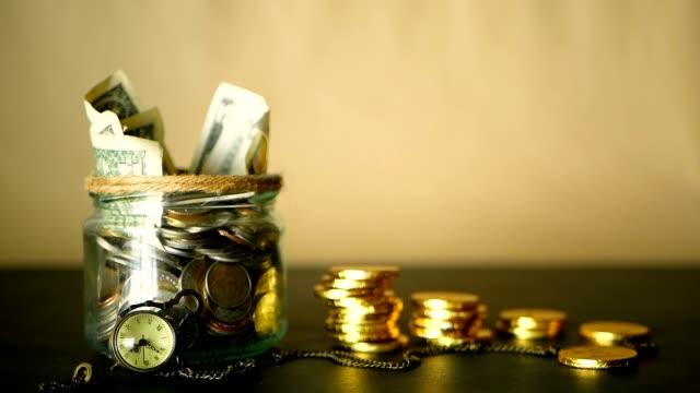spara pengar mynt i burk. symbolen för att investera, att hålla pengar koncept. samla cash sedlar i glas burk som sparbössa - ancient white background bildbanksvideor och videomaterial från bakom kulisserna