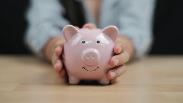 vídeos de stock e filmes b-roll de saving money concept, women hand hold a piggy bank on wooden table. close up. - economia