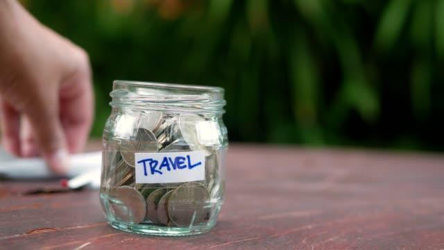 saving money in glass jarfor travel concept - dollar bill стоковые видео и кадры b-roll