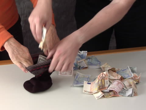Savings in a sock Two people putting their savings, a bunch of Euro bills, into a sock and ties it with a knot sock stock videos & royalty-free footage