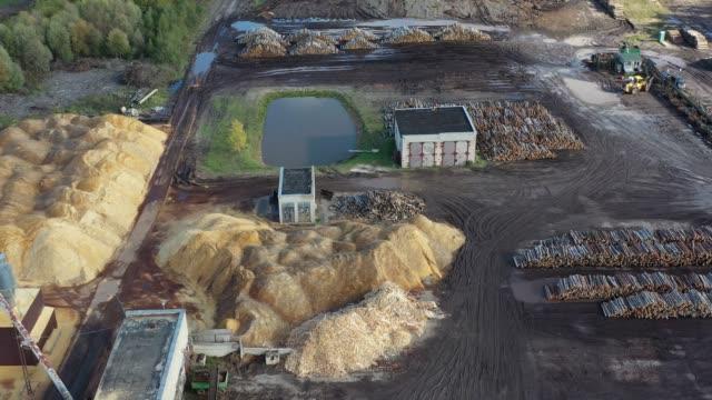 vista aerea della segheria con pile di tronchi di legno e colline di segatura con macchinari - segatura video stock e b–roll