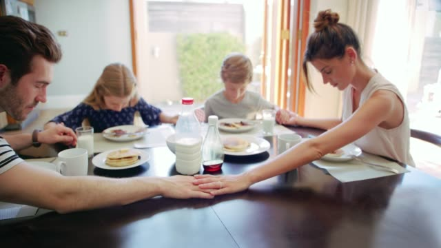 Saying grace before breakfast 4k video footage of a young family of four praying before eating breakfast together at home prayer stock videos & royalty-free footage