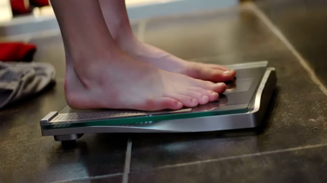 Scales Close up stock video clip using a crane of a pair of women's feet stepping onto bathroom scales as she weighs herself. As she walks across the shower room floor we see clothes being dropped behind her in an effort to lose as much weight as possible. fat nutrient stock videos & royalty-free footage