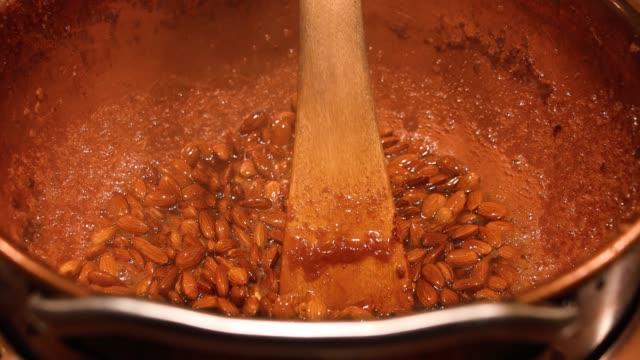 skandinavisk julmarknad - matlagning mandlar i karamell. begreppet jultradition. kallt väder komfort mat koncept. - liseberg bildbanksvideor och videomaterial från bakom kulisserna