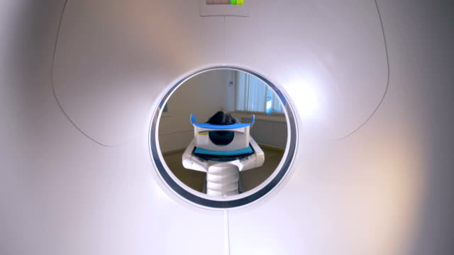 MRI scanner, tomograph with patient getting medical exam.