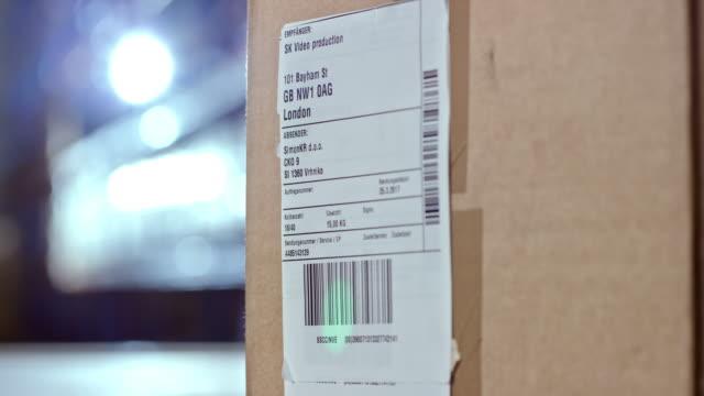 scannen eines codes auf einen versandaufkleber - etikett stock-videos und b-roll-filmmaterial
