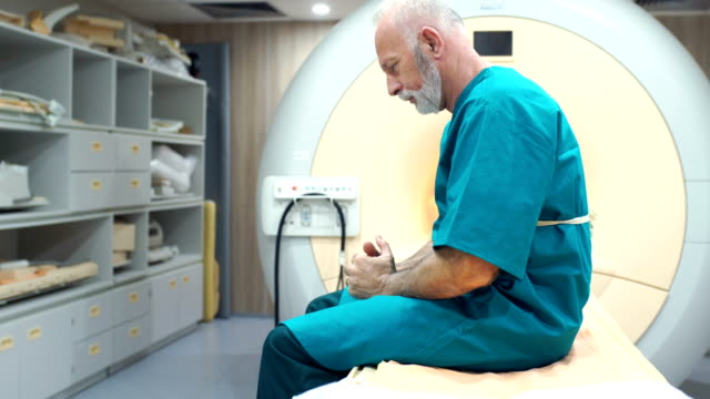 MRI scanning procedure 4k Closeup of a senior man at an MRI scanning clinic waiting to be examined and hoping for the best. His mind is full of doubts and uncertainty at the moment. cancer patient stock videos & royalty-free footage