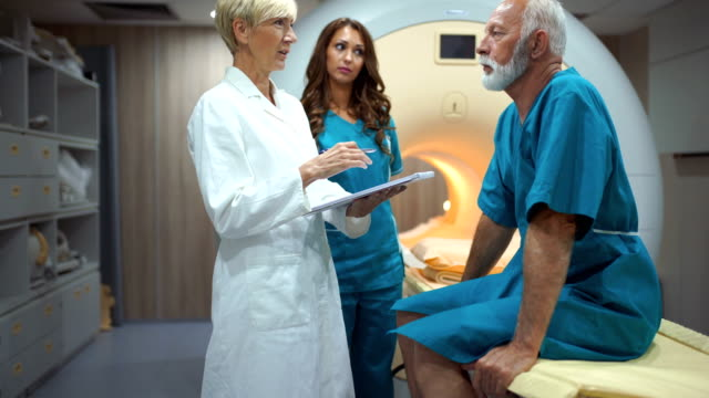 MRI scanning procedure. Closeup of a senior female doctor and technician preparing a senior male patient for an MRI scan of a torso. The doctor is explaining the procedure to the patient and that there's nothing to be afraid of. cancer patient stock videos & royalty-free footage