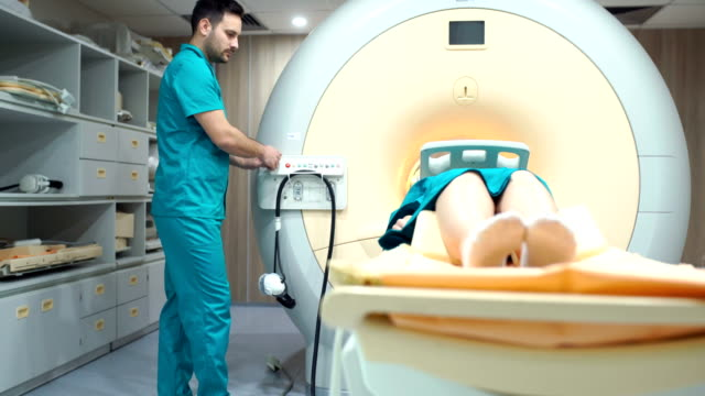 MRI scanning procedure. Closeup side of a technician preparing an early 40's female patient for brain MRI scan. The technician is at the control panel and moving the patient into the MRI tunnel. tomography stock videos & royalty-free footage