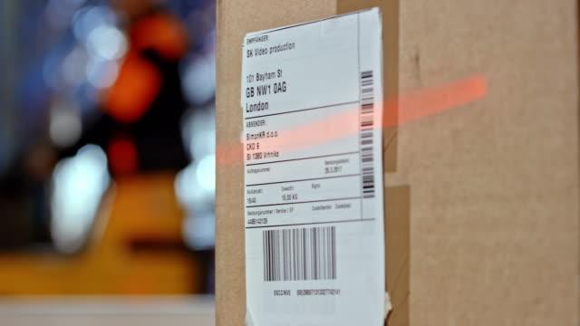 scannen den code auf dem versandetikett eines pakets - etikett stock-videos und b-roll-filmmaterial