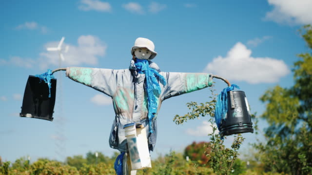 A scarecrow against a blue sky with clouds. Keeps the garden from birds and other pests video