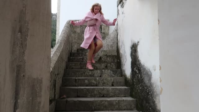 scared blonde woman running down the stairs in a pink raincoat, concept of stalking, maniac