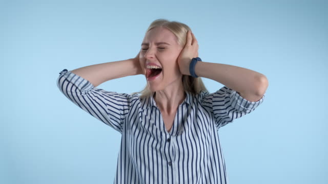 Scared desperate woman screaming and covering ears on blue background