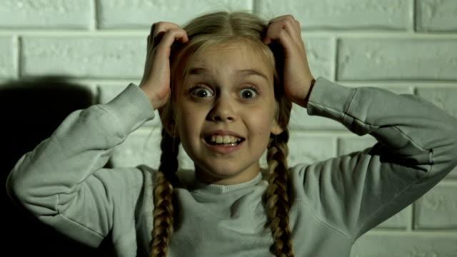 vídeos de stock e filmes b-roll de scared girl screaming holding head with hands, psychological trauma, nightmare - crianças todas diferentes