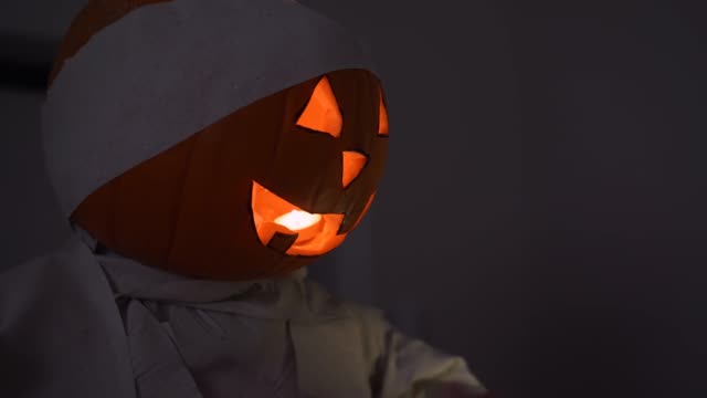 Scared guy in pink pajamas with flashlight on smartphone sneaks through dark abandoned house and suddenly comes across large doll with pumpkin jack lantern instead of head with burning candle inside.
