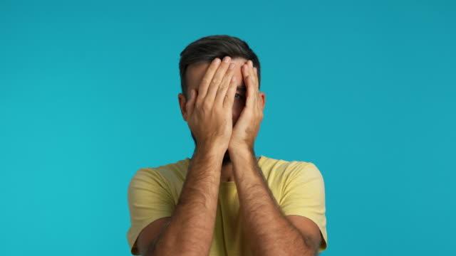 vidéos et rushes de homme effrayé couvrant le visage avec des mains et regardant par ses doigts - innocence