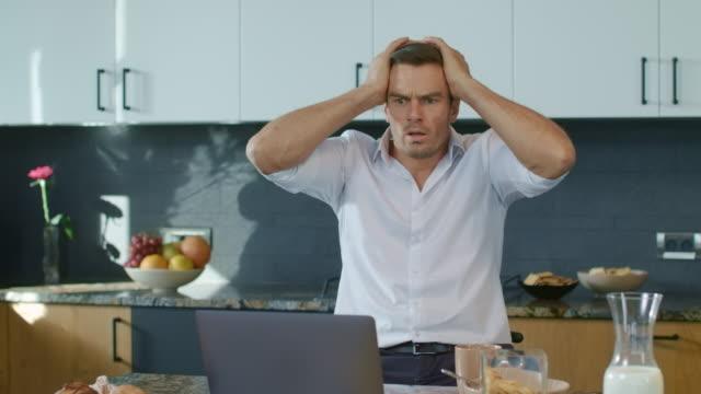 vidéos et rushes de homme effrayé regardant la vidéo sur l'ordinateur portatif dans la maison de luxe. homme d'affaires obtenant le choc - cuisine non professionnelle