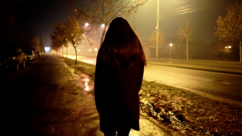 Scared of night fog Young woman is nervously looking over shoulder while walking down the street on a foggy night following moving activity stock videos & royalty-free footage