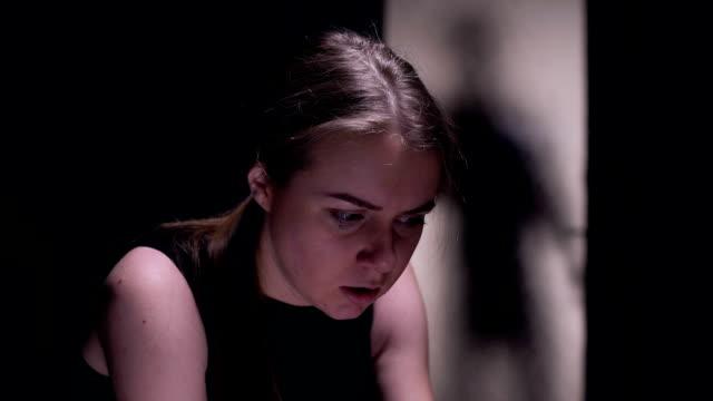 vídeos y material grabado en eventos de stock de víctima de la violencia asustada mujer sentada en la habitación, silueta de criminal fuera - human trafficking