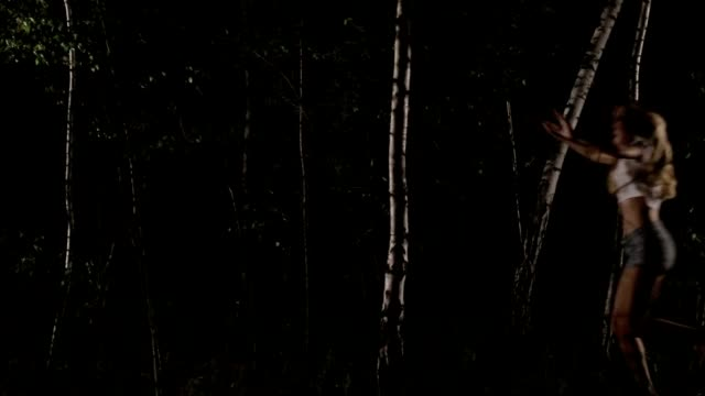 Scared woman running through forest at night video