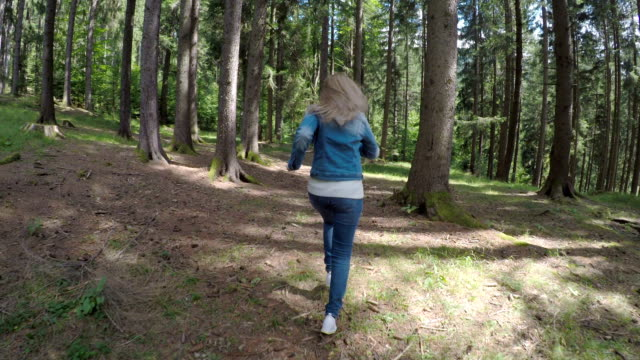 vídeos de stock e filmes b-roll de scared young girl running away to escape from danger through mountain forest - fugir