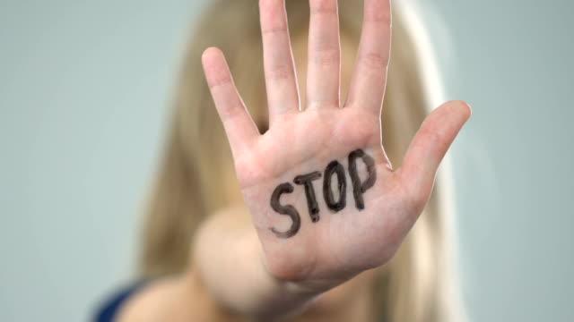 vídeos y material grabado en eventos de stock de asustado el joven mostrando señal de stop, víctima de violencia doméstica, abuso de conciencia - stop sign