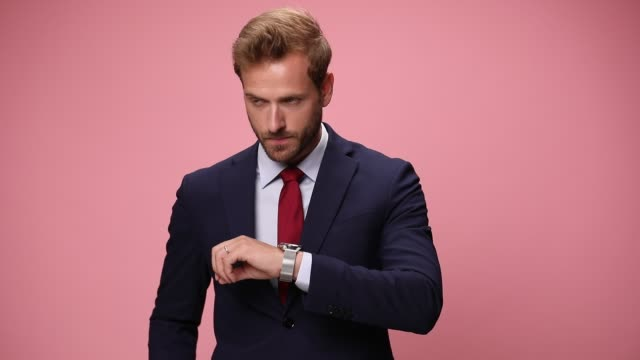 scared young man in navy blue suit checking time, being late, holding fingers to mouth, thinking, making faces and frowning, walking on pink background